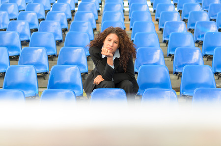 glum: Bored young woman sitting waiting in rows of empty blue seats in a stadium or auditorium with her chin resting on her hands and a glum expression Stock Photo