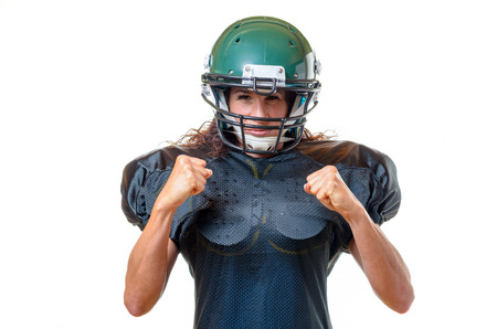 face guard: Motivated focused young female American football player wearing her uniform, helmet and face guard staring at the camera with a determined focused expression and clenched fists, isolated on white