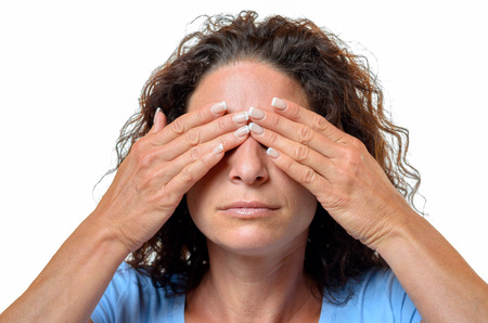 unsighted: Young woman covering her eyes with her hands in a See No Evil concept, head and shoulders isolated on white