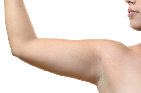Close up on a female armpit and bare upper arm of a young woman standing with her arm raised, isolated on white Stock Photo