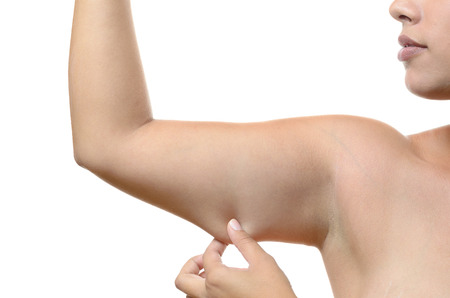 ageing: Young woman pinching the skin under her upper arm showing the tautness of her tissue and muscles, closeup isolated on white Stock Photo