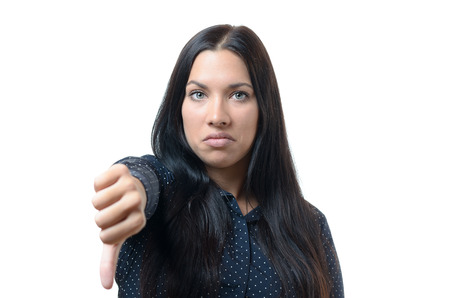 disobedient: Rebellious negative woman giving a thumb down gesture with a frown to show her displeasure and register a no vote