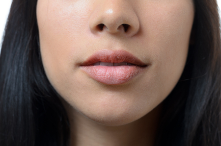 nostrils: Natural lips and mouth of a young woman with no makeup and long dark hair, close up cropped view of her lower face Stock Photo