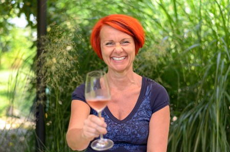 beaming: Attractive happy redhead woman toasting the camera with an elegant glass of pink champagne with a beaming smile of pleasure Stock Photo