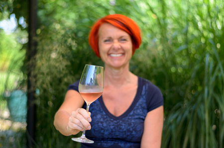 beaming: Happy redhead woman celebrating with pink champagne lifting her glass to toast the camera with a beaming smile outdoors in the garden Stock Photo