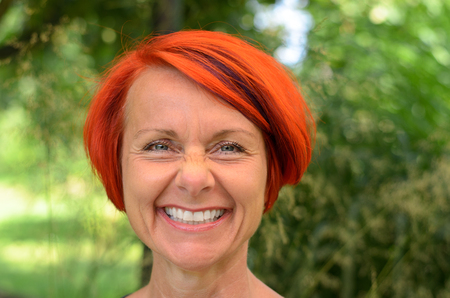 extrovert: Vivacious middle-aged redhead woman with a lovely warm beaming smile, close up head shot out doors in the garden