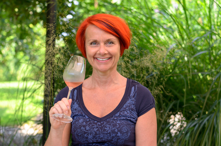beaming: Pretty redhead woman drinking a glass of pink champagne as she stands outdoors in the garden celebrating, head and shoulders smiling at the camera