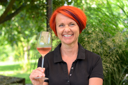 beaming: Smiling single mature woman with big smile and tall half full wineglass and red hair