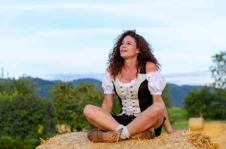 faraway: Pretty young woman sitting on a hay bale in a rural farm field looking up into the air with a faraway expression daydreaming