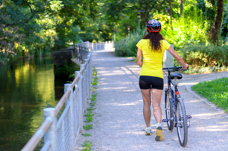 wheeling: Fit muscular woman wheeling her bicycle along a road alongside a canal or river with leafy greenery outdoors walking away from the camera