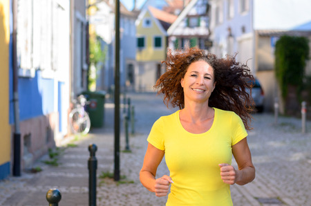 Happy young woman jogging through town along a quiet urban street with her long curly hair flying out behind her, upper body smiling at the camera