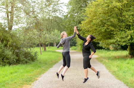 Pair of happy jumping women in workout clothes congratulating each other by slapping palms in mid air over running path