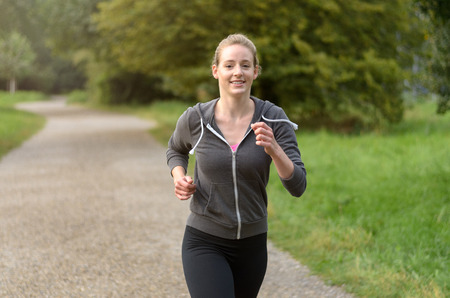 Blond young woman with smile and tied back hair running on path along trees with copy space