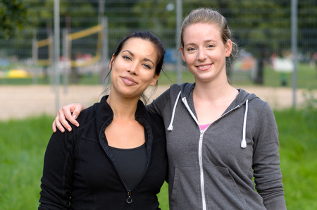 Two attractive female friends smiling and standing together in jogging jackets at park with fence
