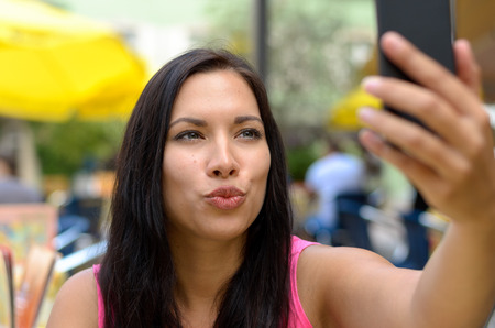 puckering lips: Woman puckering lips while taking picture of herself with cellular telephone with built in camera at outdoor cafe Stock Photo