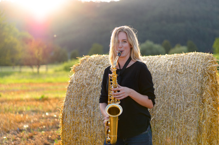 tenor: Attractive female musician playing a tenor saxophone as she leans against a round hay bale outdoors in an agricultural field