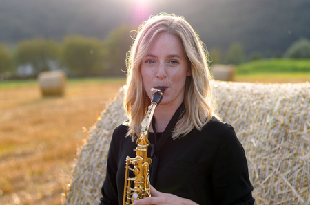 tenor: Attractive young woman playing a tenor saxophone as she stands outdoors in an agricultural field in front of a hay bale, with sun flare