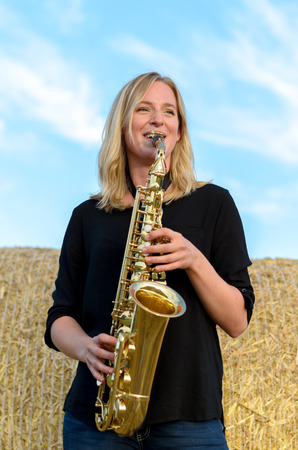 tenor: Happy attractive young blond woman standing in front of a circular hay bale outdoors playing a tenor saxophone, low angle view against cloudy blue sky
