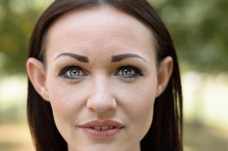 素敵なグレーの目と唇, とカメラを見つめるエルフィンの機能を備えた魅力的なブルネットの女性をクローズ アップ トリミング顔ポートレート屋外 写真素材