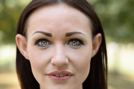 protruding eyes: Attractive brunette woman with lovely grey eyes and elfin features looking intently at the camera with parted lips, close up cropped face portrait outdoors Stock Photo