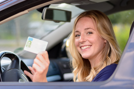 Happy young blond woman sitting behind the steering wheel of a car showing off her drivers license through the open window Foto de archivo