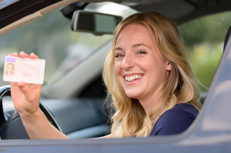 Happy young blond woman sitting behind the steering wheel of a car showing off her drivers license through the open window Фото со стока