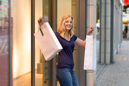 holding aloft: Happy triumphant young women shopper standing in the doorway to a clothing store holding aloft her bags full of merchandise with a proud smile