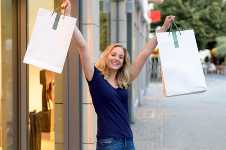 triumphant: Happy triumphant young women shopper standing in the doorway to a clothing store holding aloft her bags full of merchandise with a proud smile