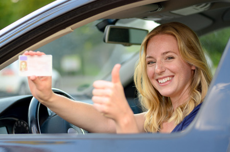 Young blond woman sitting behind the steering wheel of a car showing off her drivers license with a proud smile and thumbs up gesture