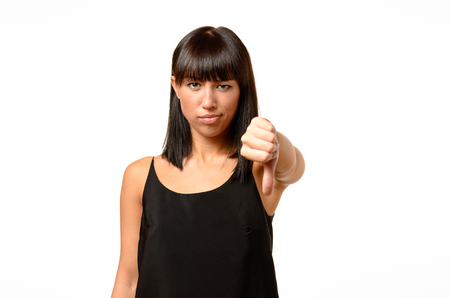 displeasure: Rebellious negative woman giving a thumbs down gesture with a frown to show her displeasure and register a no vote