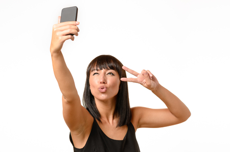 pouting: Seductive woman pouting her lips for a kiss and making a V-sign gesture with her hand while taking a selfie on a mobile phone, isolated on white