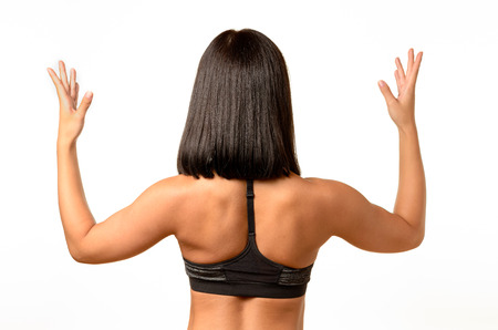 splayed: Rear view of a tanned woman with shoulder length dark hair standing with raised arms and splayed fingers , upper body isolated on white