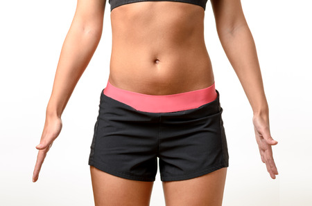 midriff: Shapely body of a young woman with a bare midriff wearing shorts and holding her hand away from her sides isolated over white Stock Photo