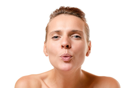 Romantic woman blowing a kiss at the camera with pouting lips and a sensual seductive expression, head and shoulders on white