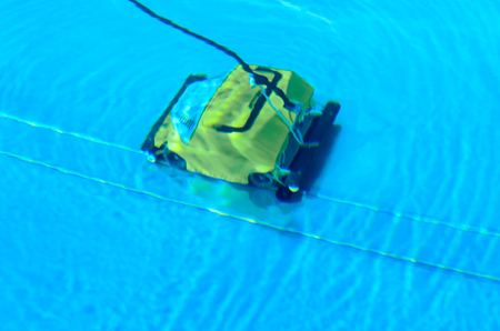 Mechanical pool cleaner suctioning and filtering the water at the bottom in a health and hygiene concept in sparkling blue water with reflections of sunlight Banque d'images