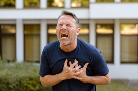 coronary: Middle-aged man suffering a heart attack or coronary infarct clasping his chest and screaming in pain outdoors in summer in a healthcare concept