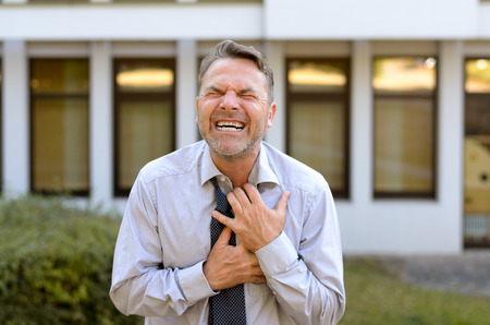 infarct: Middle-aged businessman suffering chest pains clutching his chest and grimacing as a prelude to a heart attack or myocardial infarct