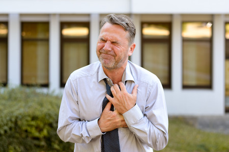 Geschäftsmann mittleren Alters leiden Schmerzen in der Brust umklammert seine Brust und verzog das Gesicht als Auftakt zu einem Herzinfarkt oder Myokardinfarkt