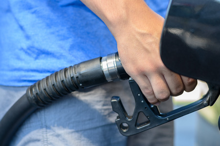 Man filling his car with gasoline at a garage or filling station, close up view on his hand and the nozzle as he dispenses the fuel
