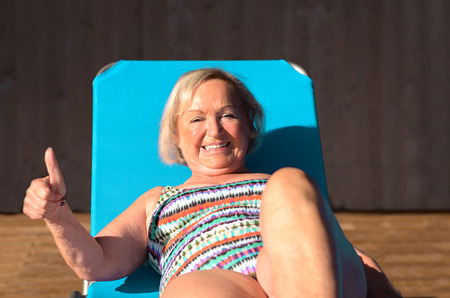 recliner: Active senior blond woman sunbathing on a recliner chair giving a thumbs up of sign of approval with a beaming smile Stock Photo