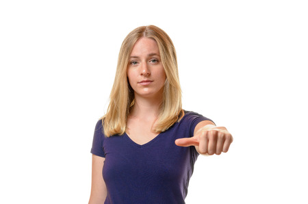 impassive: Young woman abstaining from voting giving a neutral side thumb gesture with an impassive expression, upper body isolated on white with copy space