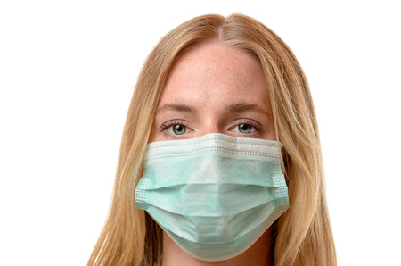 Frowning young blond woman wearing a face mask as protection against airborne diseases and pollution, close up head shot on white