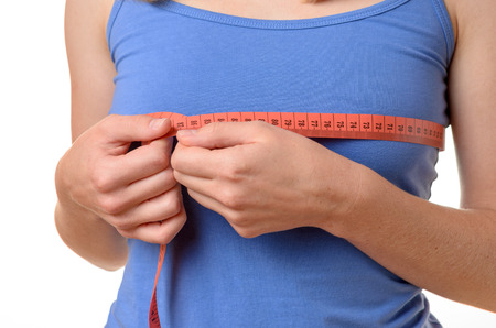 Young woman wearing a blue summer t-shirt measuring her breasts with a tape measure, close up torso view on white Stock Photo