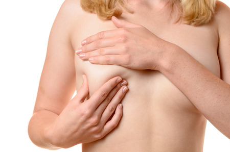 Nude young woman massaging her breast with her hand as she does a routine examination for early signs of cancer, close up cropped view