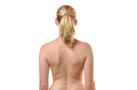 upper body: Rear view of the bare back of a curvy shapely young woman with her arms to her side, close up cropped upper body view isolated on white