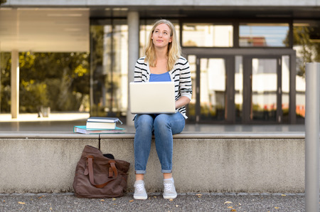daydream: Young woman in blue jeans sitting outside on barrier using laptop while looking upward as if to daydream or think about something Stock Photo