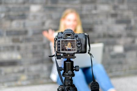 Jeune femme au foyer sur l'écran LCD de l'appareil photo numérique en agitant la main tout en étant assis sur le sol contre le mur pour le concept sur les blogs vidéo Banque d'images