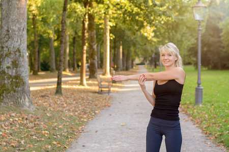 cardiovascular exercising: Smiling sporty young woman doing warming up exercises stretching her muscles before enjoying a morning jog through a park and woodland in an active lifestyle concept