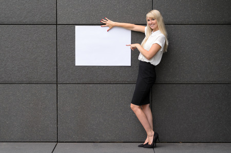 tiled wall: Friendly elegant businesswoman displaying a blank white rectangular sign holding it up against a grey tiled wall of an office building with a happy smile with copy space for your text