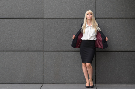 reveal: Stylish professional woman opening her suit jacket to reveal her crisp white blouse and shapely body as she leans against a grey tiled commercial wall with copy space